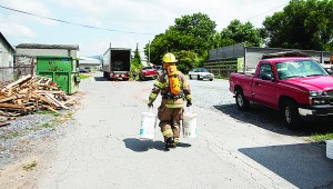 Photo by Brandon Hicks A firefighter carries supplies to the site of a hazardous material spill near downtown Elizabethton Friday.