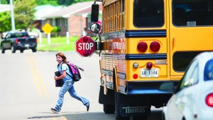 A bus rider takes a cautious look for traffic while crossing the street at the end of the school day. Law enforcement is reminding drivers to use extra caution and to obey traffic laws when they encounter a school bus which has stopped to load or unload students.
