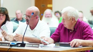 Commissioners Joel Street, left, and Richard Winters look over product samples from STL Distribution. The Commission approved a 5-year tax abatement plan for STL Distribution on a vote of 22-1.