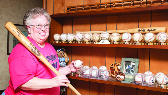 Photo by Brandon Hicks Paula Bishop shows off her collection of Twins memorabilia, which includes autographed baseballs from local players. Twins Manager Ray Smith has given Bishop a baseball autographed by Twins players each year since 1988.