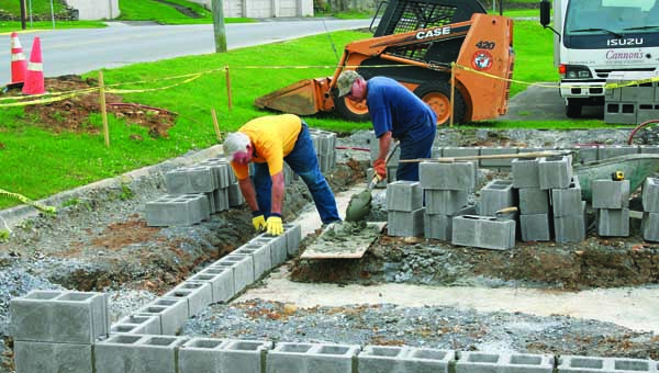 Star Photo/Abby Morris-Frye  Carter County Car Club members Randy Payne, left, and Lynn Taylor work to lay block for the bathrooms being constructed downtown as a joint partnership between the club and the City of Elizabethton.