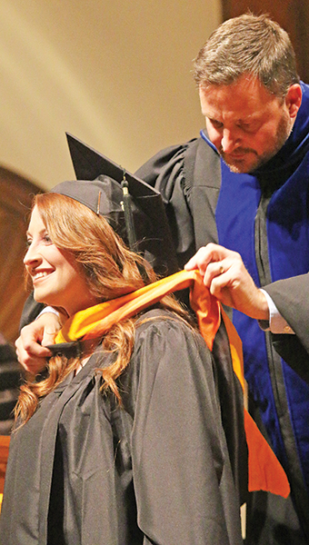 Star Photo/Curtis Carden                           Kelsie Deaton, a graduate of Happy Valley High School, received her hood from Dr. Jeff Snodgrass, director of Occupational Therapy, for graduating with a master's degree in the OT field.