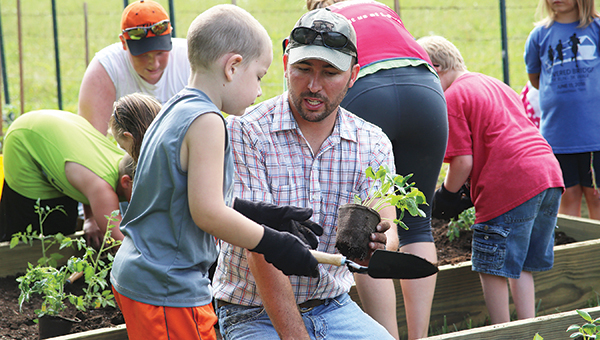 Unaka agricultural teacher Josh Armentrout works with a student involved with the Carter Cares summer program.